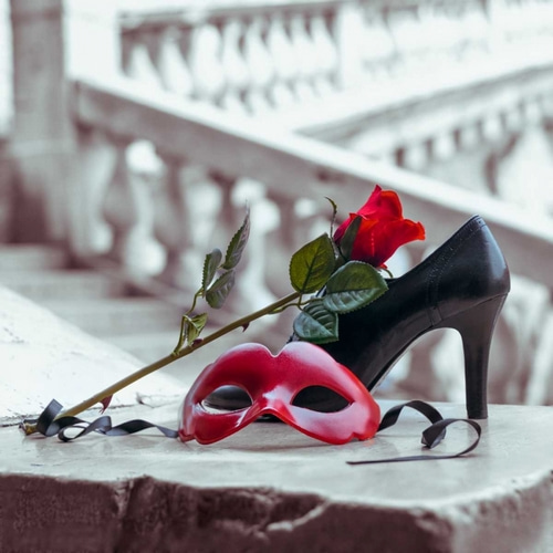 Venetian mask and high heel shoe with red rose, Rialto bridge, Venice, Italy